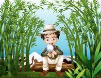 Ein Regenwald mit einem Mann, der eine Vergrößerungslinse hält Lizenzfreie Stockfotografie