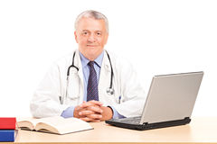 Ein reifer Doktor in seiner Büroaufstellung Lizenzfreies Stockbild