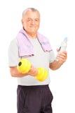 Ein reifer Mann, der mit einem Dumbbell trainiert und eine Flasche anhält   stockfotos