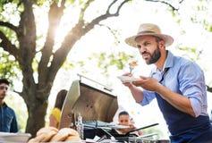 Ein reifer Mann mit der Familie und Freunden, die Lebensmittel auf einer Grillpartei kochen und dienen stockbild