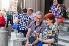 Ein reifes Paar, das auf einer Bank und einem aufpassenden Smartphone sitzt stockfoto