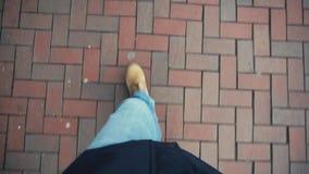 Ein Reisender in den Jeans und in den gelben Stiefelwegen auf Pflastersteinen Tio-Ansicht stock video footage