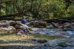 Ein Reisender, der in einem Fluss stillsteht Lizenzfreies Stockfoto