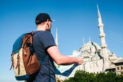 Ein Reisender in einer Baseballmütze mit einem Rucksack betrachtet die Karte nahe bei der blauen Moschee - der berühmte Anblick v stockfotografie