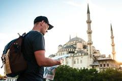 Ein Reisender in einer Baseballmütze mit einem Rucksack betrachtet die Karte nahe bei der blauen Moschee - der berühmte Anblick v lizenzfreie stockfotos