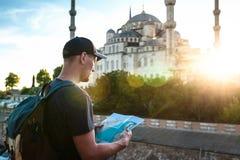 Ein Reisender in einer Baseballmütze mit einem Rucksack betrachtet die Karte nahe bei der blauen Moschee - der berühmte Anblick v lizenzfreie stockfotografie