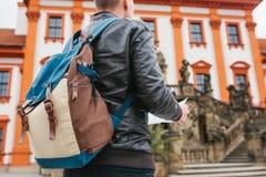 Ein Reisender mit einem Rucksack betrachtet die Karte nahe bei dem Schloss in der Tschechischen Republik Tourismus und Besichtigu stockfoto