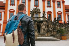 Ein Reisender mit einem Rucksack betrachtet die Touristenattraktion Der Tourist betrachtet das Schloss in der Tschechischen Repub lizenzfreie stockbilder
