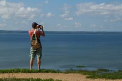 Ein Reisender mit einem Rucksack hinter ihm steht auf einem Hügel und macht ein Foto des Sees lizenzfreie stockfotografie