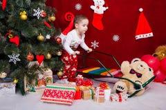 Ein reizend Junge rollt einen Pferdeschlitten nahe bei vielem Weihnachtsgeschenk Stockbilder