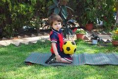 Ein reizender kleiner Junge, der bei einer gelben Kugel liegt Stockfotos