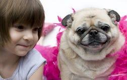 Ein reizendes entzückendes junges Kind mit Pug lizenzfreie stockbilder