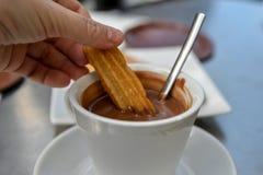 Ein reizendes Frühstück, eine heiße Schokolade und ein Churro lizenzfreie stockbilder