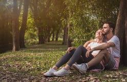Ein reizendes Paar, das in einen Park streichelt lizenzfreie stockfotos