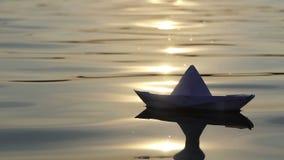 Ein reizendes Papierboot schwimmt in einen Waldsee bei Sonnenuntergang in SlomO stock video footage