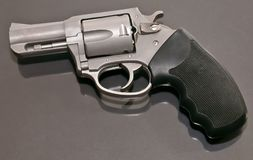 Ein Revolver des Edelstahls 44spl, der nach einer Glasoberfläche legt stockfoto