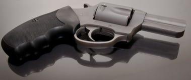 Ein Revolver des Edelstahls 44spl, der nach einer Glasoberfläche legt stockbild