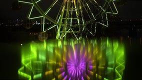 Ein Riesenrad mit farbigen Lichtern an der Nacht und an seiner unscharfen Reflexion stock footage