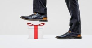 Ein riesiger Geschäftsmannstiefel bereit, auf eine weiße Geschenkbox mit einem roten Bogen zu treten lizenzfreie stockfotos