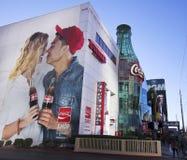 Ein riesiges Cola-Zeichen und eine Flasche auf dem Streifen Lizenzfreie Stockbilder