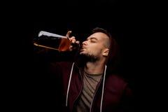 Ein Risikomann trinkt Whisky auf einem schwarzen Hintergrund Ein deprimierter Kerlabhängiger auf Alkohol Kopieren Sie Platz Lizenzfreie Stockfotos