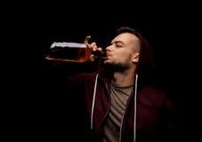 Ein Risikomann trinkt Whisky auf einem schwarzen Hintergrund Ein deprimierter Kerlabhängiger auf Alkohol Kopieren Sie Platz Stockfoto