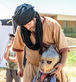 Ein Ritterfestivalteilnehmer hilft einem kleinen Besucher, Rüstung in Goren-Park in Israel zu kleiden Lizenzfreies Stockfoto