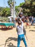 Ein Ritterfestivalteilnehmer kleidete in den Kämpfen eines Samuraikostüms mit einem kleinen Besucher auf Schaumgummiklingen in Go Stockbild