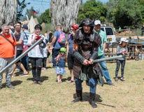 Ein Ritterfestivalteilnehmer kleidete in einem Samuraikostüm an, das für einen Kampf mit einer Schaumklinge mit einem Besucher in lizenzfreie stockbilder