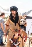 Ein Ritterfestivalteilnehmer wirft mit einem kleinen Besucher auf, der in der Rüstung in Goren-Park in Israel gekleidet wird Stockfoto