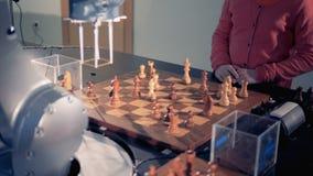 Ein Roboterarm und ein kleines Mädchen ordnen Schachfiguren neu stock footage