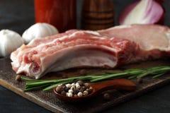 Ein rohes Stück Schweinefleischsteak mit Rosmarin, Knoblauch, Zwiebel und Pfeffer Stockfoto