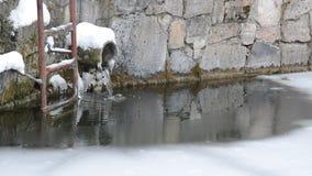 Ein Rohr von der einer Wand Wasserströme in den See, eingefroren im Winter durch Eis stock footage
