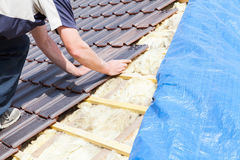 Ein Roofer, der Fliese auf das Dach legt Lizenzfreie Stockfotos