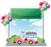 Ein rosa Eiscremebus nahe einem leeren grünen Brett Lizenzfreies Stockfoto