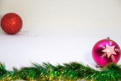 Ein Rosa, ein rote Weihnachtsbälle und Weihnachtsdekoration auf einem weißen Hintergrund Stockfotos