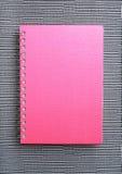 Ein rosafarbenes Notizbuch auf Wandverkleidung Stockfotografie