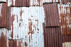 Ein rostiges und verwittertes schauendes Stück gewölbter Metallhintergrund und -c$beleuchten Stockfoto