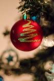 Ein Rot Bobble die Weihnachtsverzierung, die von einem Draht hängt Stockbild