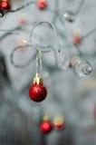 Ein Rot Bobble die Weihnachtsverzierung, die von einem Draht hängt Lizenzfreies Stockbild
