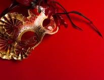 Ein Rot und ein Gold versahen venetianische Maske auf rotem Hintergrund mit Federn Lizenzfreie Stockbilder