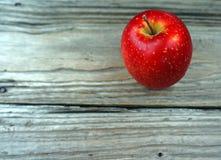 Ein roter Apfel auf Holztisch lizenzfreie stockbilder