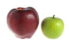 Ein roter Apfel und ein grüner Apfel abgedeckt durch Wassertropfen Lizenzfreie Stockfotos