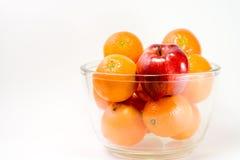 Ein roter Apple und Orangen in einer Schüssel Stockbild