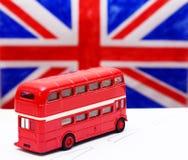 Ein roter Doppeldeckerbus und -flagge Lizenzfreies Stockfoto