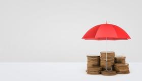 Ein roter offener Regenschirm vertikal gesetzt über einige Stapel der goldenen Münzen auf weißen Hintergrund Lizenzfreies Stockfoto
