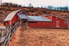 Ein roter Pferdebauernhof mit einem Zaun Lizenzfreies Stockfoto