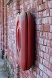 Ein roter Rettungsgürtel auf einer Wand des roten Backsteins lizenzfreie stockfotografie