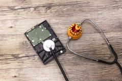 Ein roter Schraubenzieher kuriert eine defekte Festplatte mit Stethoskop lizenzfreies stockbild