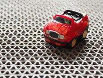 Ein roter SpielzeugParkplatz auf rauem Boden Stockfotos